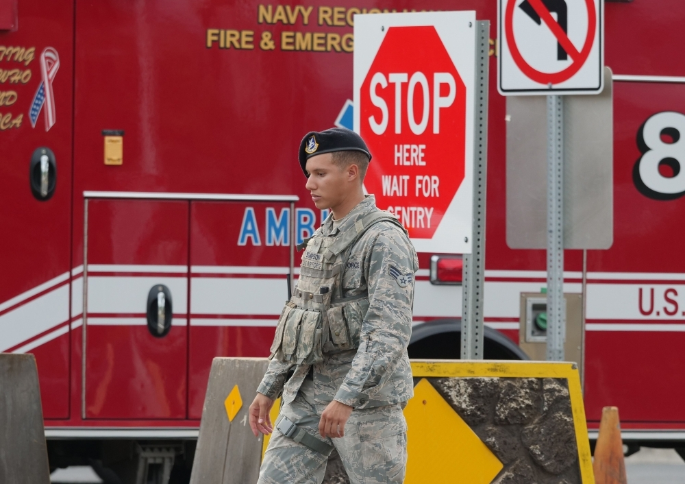 A security guard walks past a naval emergency ambulance responding to a fatal shooting at the Pearl Harbor Naval Shipyard, on Oahu, Hawaii, on Wednesday. — AFP