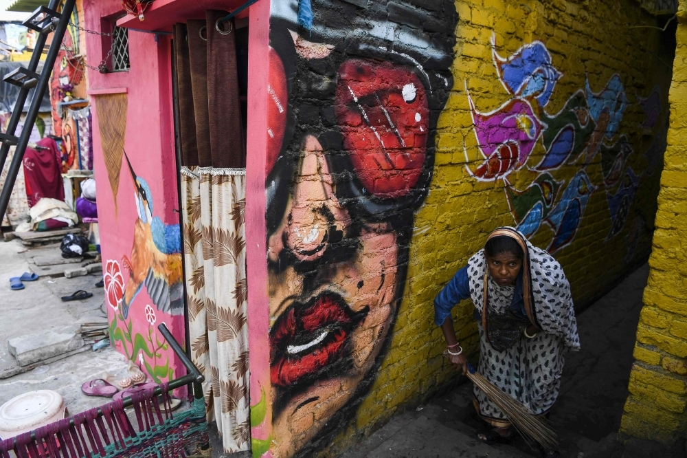 Local residents shop from a store next to a home adorned with a mural painted by artists from 'Delhi Street Art' group at the Raghubir Nagar slum in New Delhi in this Dec. 2, 2019 file photo. — AFP