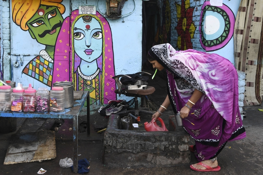 A woman collects water in front of a home adorned with a mural painted by artists from 'Delhi Street Art' group at the Raghubir Nagar slum in New Delhi in this Dec. 2, 2019 file photo. — AFP