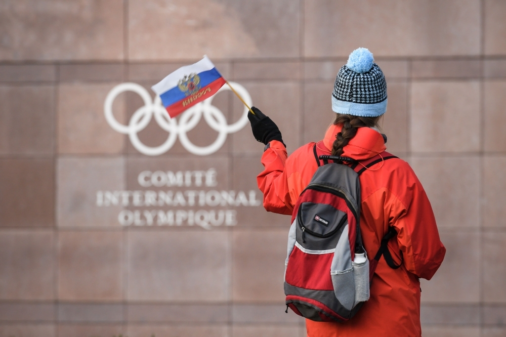 In this file photograph taken on Dec. 5, 2017, a supporter waves a Russian flag in front of the logo of the International Olympic Committee (IOC) at their headquarters in Pully near Lausanne. In Russia, where criticism of the authorities can lead to dire consequences, the head of the country's anti-doping agency Yury Ganus has openly accused officials of tampering with data handed to the global watchdog. — AFP