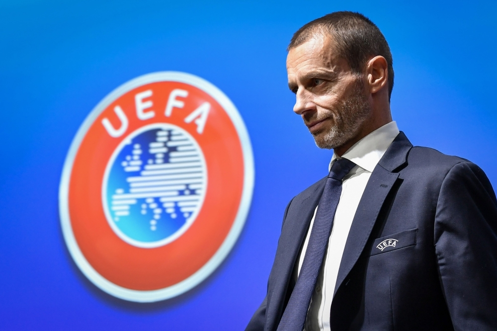 UEFA president Aleksander Ceferin walks past a sign with the UEFA logo after attending a press conference following a meeting of the executive committee at the UEFA headquarters, in Nyon, Switzerland on Wednesday. — AFP