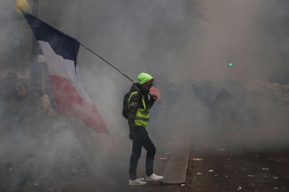 A man holding a French flag and a yellow vest walks in tear gas during a rally against the pension overhauls, in Paris, on December 5, 2019 as part of a nationwide strike.  Trains cancelled, schools closed: France scrambled to make contingency plans on for a huge strike against pension overhauls that poses one of the biggest challenges yet to French President's sweeping reform drive. / AFP / Zakaria ABDELKAFI