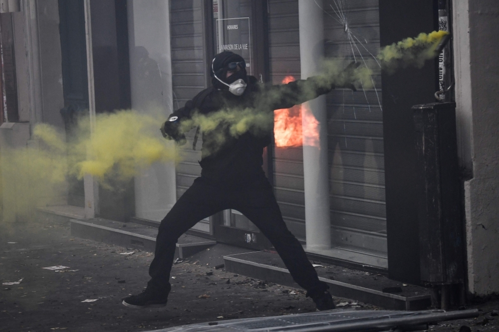A protester throws a yellow flare during a rally against the pension overhauls, in Paris, on Thursday. — AFP