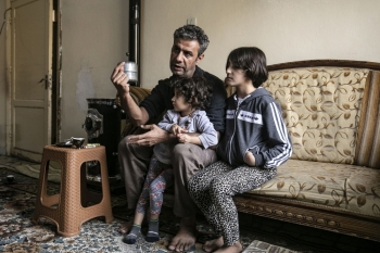 Displaced from the border town of Ras Al-Ain, Syrian Kurdish film director Teymour Ifdaki, 42, who's home was allegedly burned along with his collection of 500 books by Turkey-backed Syrian fighters, sits with his two daughters in a house in the de-facto Syrian Kurdish capital of Qamishli, in this Nov. 28, 2019 file photo. — AFP