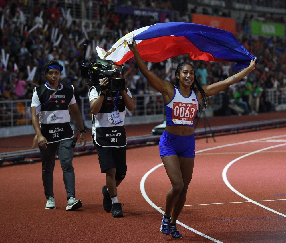 Kristina Marie Knott from the Philippines celebrates after winning in the women's 200m athletics event at the SEA Games (Southeast Asian Games) at the athletics stadium in Clark, Capas, Tarlac province north of Manila, on Saturday. — AFP