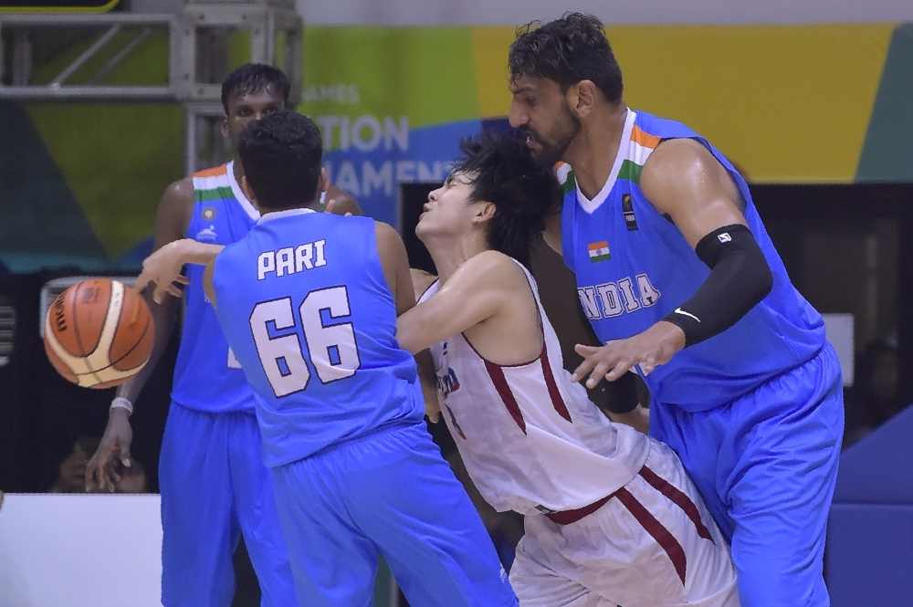 In this file photo taken on Feb. 8, 2018, Attapong Leelaphipatkul [white No. 98) of Thailand vies for the ball against Akilan Pari (No. 66) and Satnam Singh Bhamara (R) of India during the basketball round robin at the test event for 2018 Asian Games in Jakarta. Satnam Singh, the first Indian to be drafted into the NBA, has been provisionally suspended by India's anti-doping agency after failing a drug test last month. — AFP