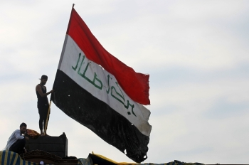 An Iraqi demonstrator waves a large national flag in the capital Baghdad's Tahrir Square, amid ongoing anti-government protests, on Friday. -AFP.