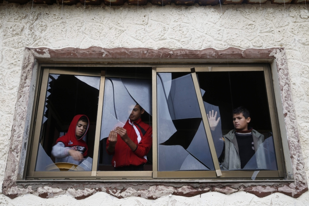 Palestinian boys pull shards of glass from a broken window at their home near the site of Israeli overnight attacks in Gaza City on Sunday. -AFP