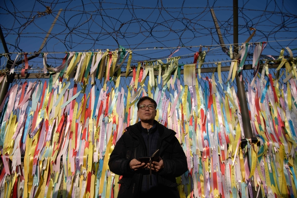 Hwang In-cheol stands before a fence covered in 'peace ribbons' during an event calling for the release of his father by North Korea, at the Imjingak peace park near the Demilitarized Zone (DMZ) separating the two Koreas, in Paju on Sunday. -AFP
