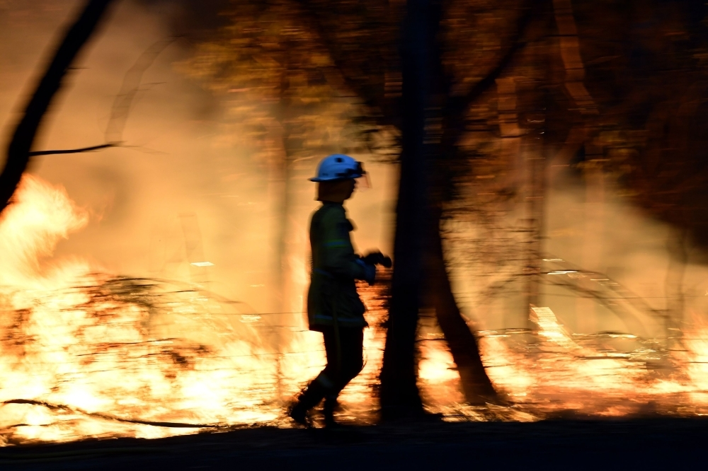 This photo taken on Saturday shows firefighters conducting back burning measures to secure residential areas from encroaching bushfires at the Mangrove area, some 90-110 kilometers north of Sydney.  -AFP