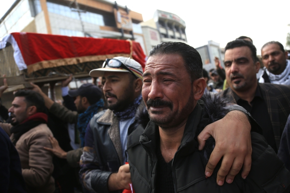 An Iraqi mourner cries as he joins the crowd walking in the funeral of a prominent civil society activist who was shot dead the previous night while returning home from anti-government protests, in Iraq's shrine city of Karbala, south of the capital Baghdad, on Monday. — AFP