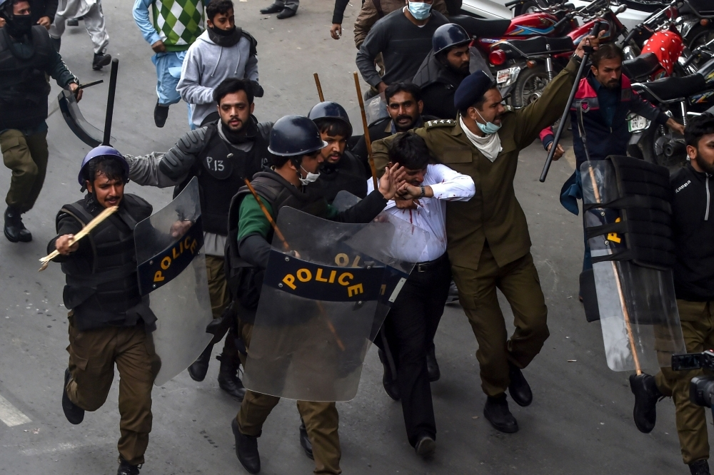 Policemen detain a lawyer, center in white shirt, following a clash between lawyers and doctors in Lahore, Pakistan, on Wednesday. — AFP