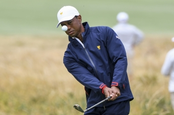 US team captain Tiger Woods hits to the green during a practice round ahead of the Presidents Cup golf tournament starting on Dec. 12, in Melbourne, on Wednesday. — AFP
