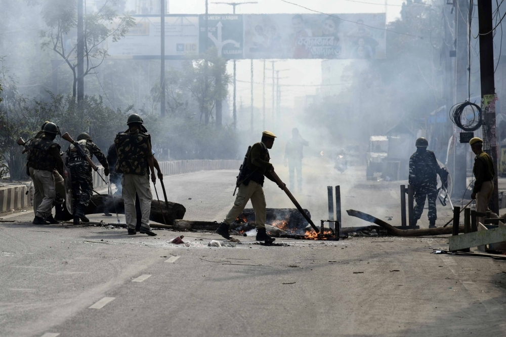 Police officers remove a burning blockade from a road in Guwahati, Assam, on Thursday. — AFP