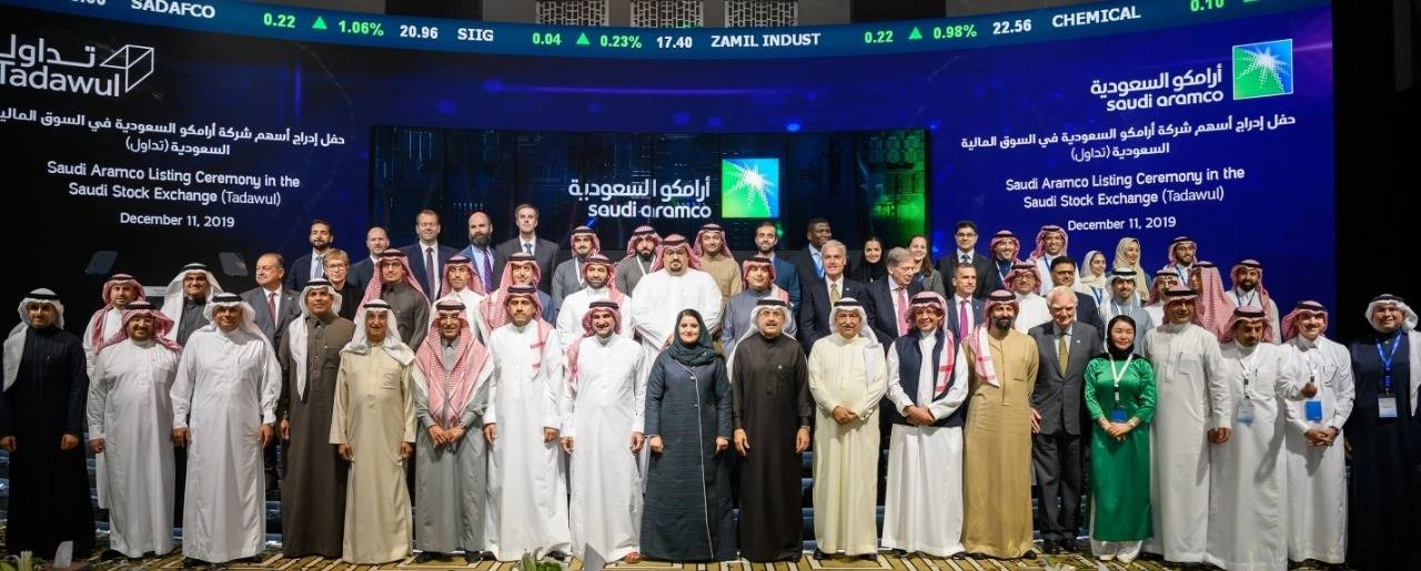 Saudi Aramco and Tadawul top officials are seen during the first day of oil giant's trading on Wednesday in Riyadh.