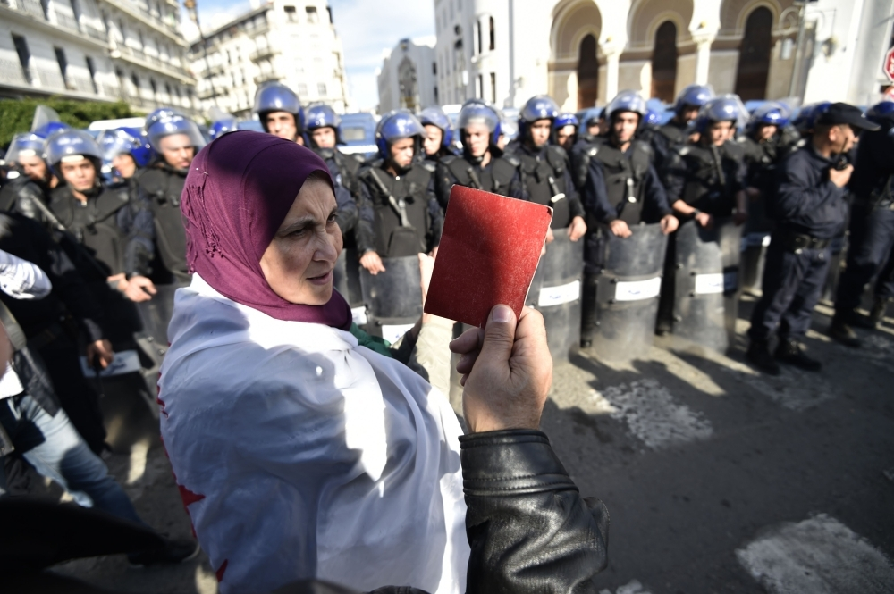 An Algerian protester holds up a red card during an anti-government demonstration in the capital Algiers on Wednesday. — AFP