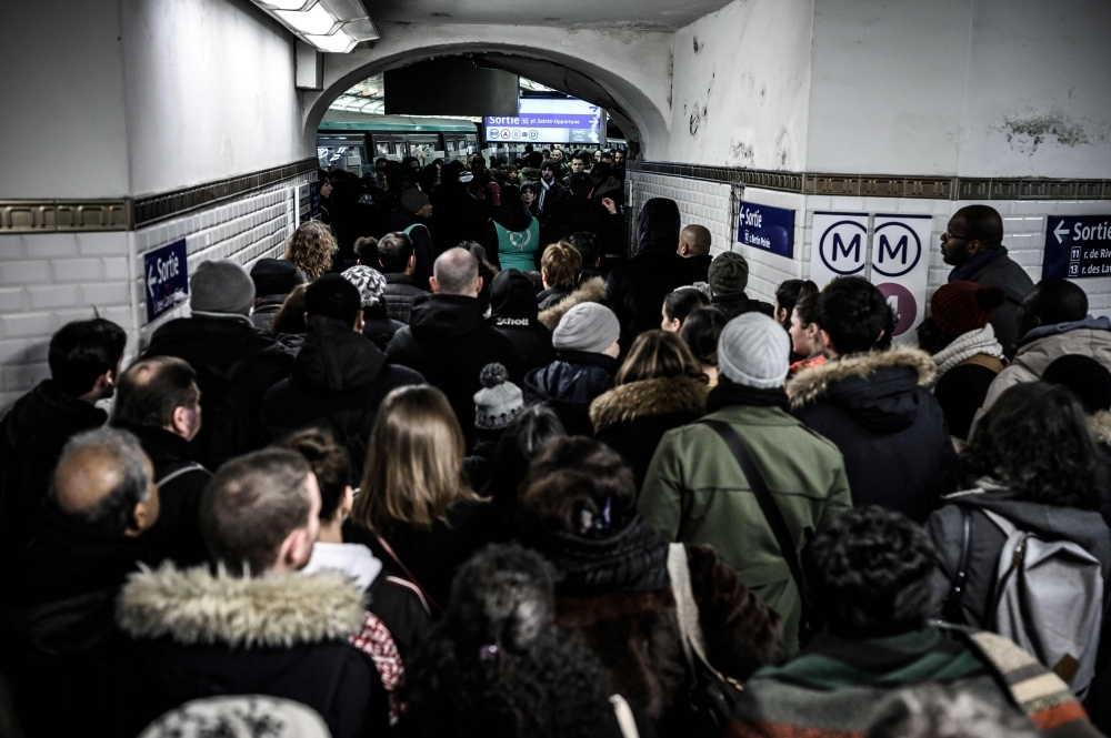 Commuters queue to access the platform of the subway line 1 during a strike of public transports operator SNCF and RATP employees over French government's plan to overhaul the country's retirement system, as part of a nation-wide movement, in Paris on Thursday. — AFP