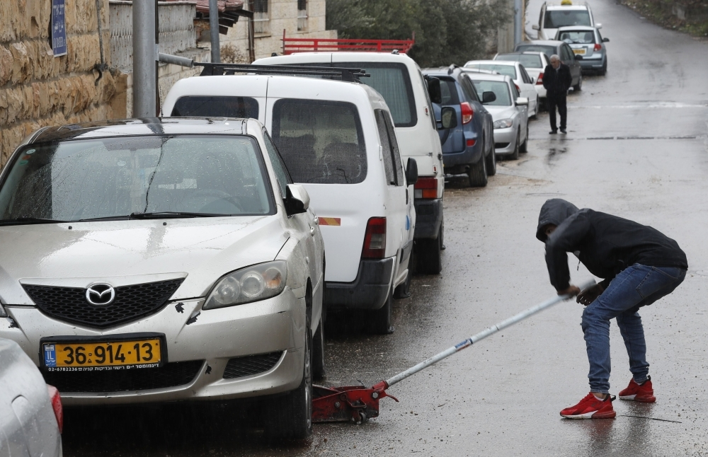 A Palestinian youth checks a car as vehicles with their tires slashed are pictured in the Palestinian neighborhood of Shuafat, neighboring the Israeli settlement of Ramat Shlomo, in Israeli annexed east Jerusalem, in this Dec. 9, 2019 file photo. — AFP
