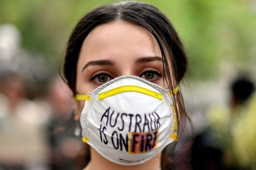 A demonstrator with a mask attends a climate protest rally in Sydney on Wednesday. — AFP