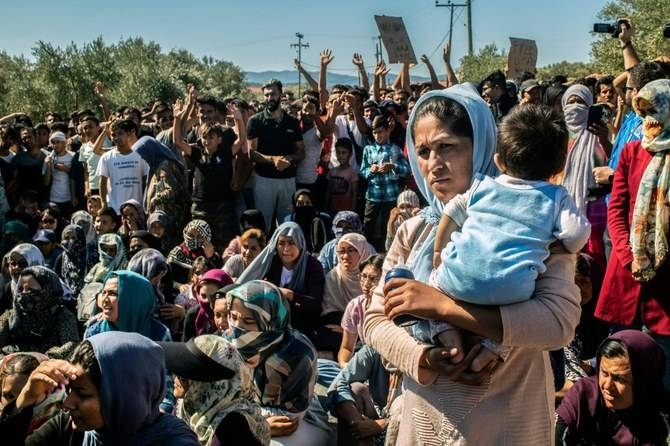 A woman holds a baby as refugees and migrants take part in a demonstration against their living conditions at the Moria camp on the island of Lesbos, Greece, in this Oct. 1, 2019 file photo. — AFP