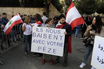 Lebanese anti-government demonstrators hold placards outside the French embassy in the capital Beirut to protest against the UN-created International Support Group (ISG) for Lebanon meeting taking place in Paris on Wednesday. — AFP