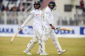Sri Lankan batsmen walk off the pitch at the close of play during the first Test against Pakistan in Rawalpindi, as heavy rain and bad light hit the second day.