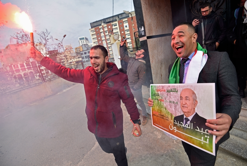 Supporters of presidential candidate Abdelmadjid Tebboune celebrate his victory in Algeria's presidential election in Algiers on Friday. — AFP