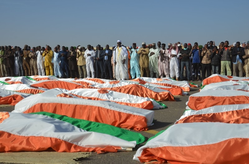 The Imam of the Great Mosque of Niamey, Cheikh Djabir Ismael, center, who led the funeral prayer, stands in front of the bodies of military personnel at the Niamey Airforce Base in Niamey, on Friday. — AFP