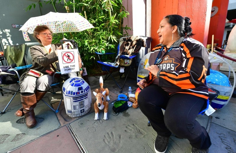 Star Wars fans  Stefanice Vance, left and Veronica Nunez, right, chat while waiting in line outside the TCL Chinese Theater in Hollywood, California, on Friday, where many have been waiting since December 10 over a week in advance of the December 19 opening of the latest Star Wars film