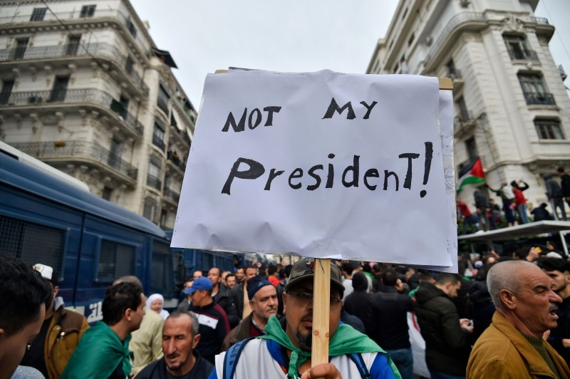 An Algerian protester lifts a placard in the capital Algiers on Friday, as he takes part in a demonstration to reject the results of the presidential elections. — AFP