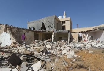 Libyans check the site of an air strike on the southern outskirts of the capital Tripoli in this October 14, 2019 file photo. — AFP