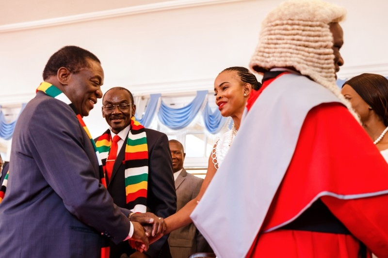 Zimbabwe's President Emmerson Mnangagwa, left, shakes hands with Mary Chiwenga, wife of newly appointed Vice President Constantino Chiwenga, as also newly appointed Vice-President Kembo Mohadi looks on after a swearing-in ceremony for Zimbabwe's new vice presidents by the country's Chief Justice at the State House in Harare in this Aug. 30, 2018 file photo. — AFP