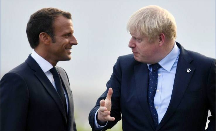 France's President Emmanuel Macron, left, and UK's Prime Minister Boris Johnson, right,  along with the world leaders were poised to commit to ending all foreign meddling in Libya's war at a Berlin summit Sunday.