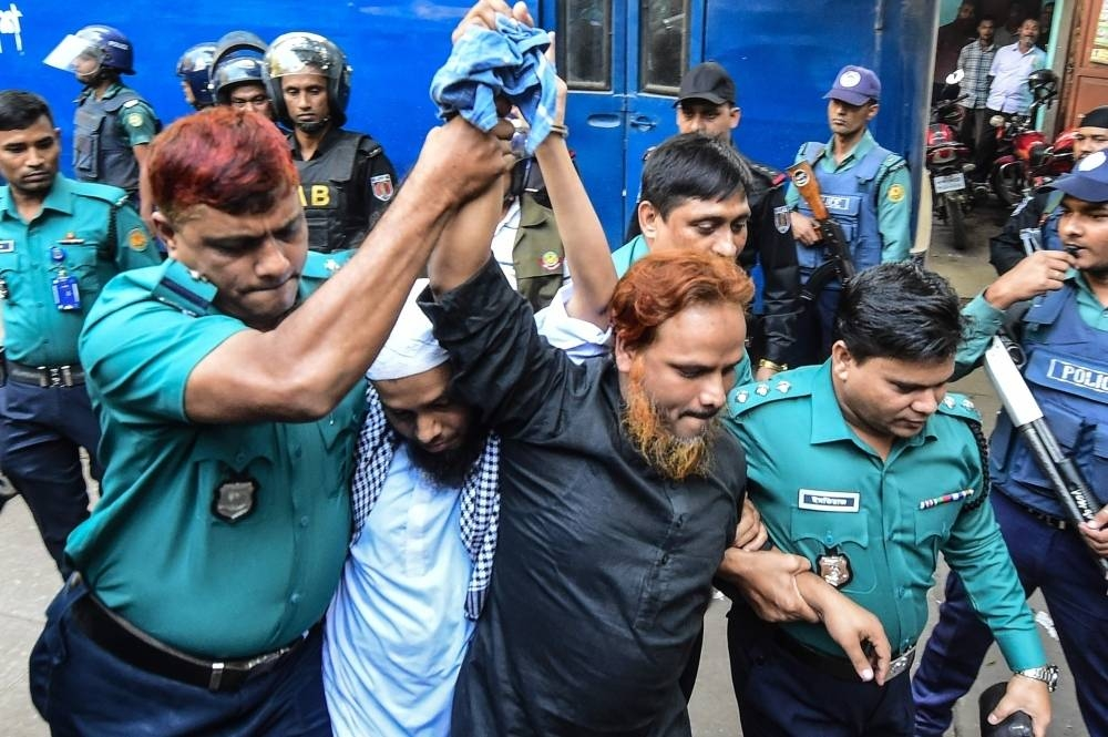 Police escort extremists, center, accused of allegedly plotting the Holey Artisan Bakery cafe attack, carried out by militants, to a courtroom for their trial in Dhaka in this file photo. — AFP