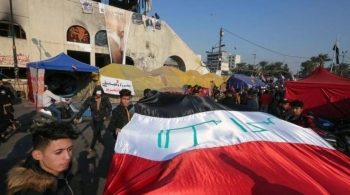 Iraqi anti-government protesters carry a large national flag during ongoing demonstrations in the capital Baghdad's Tahrir square in this file photo. — AFP