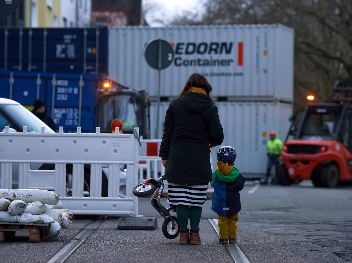 A woman and child stand in front of a wall made up of containers erected by workers to protect the houses in a street where World War II bombs were discovered in Dortmund, western Germany. — AFP