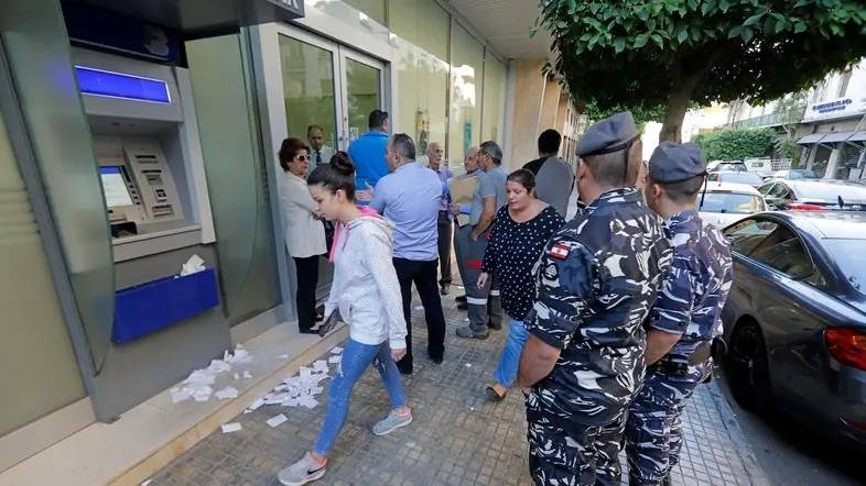 People await to enter a bank that has just reopened in the center of the Lebanese capital Beirut. — AFP