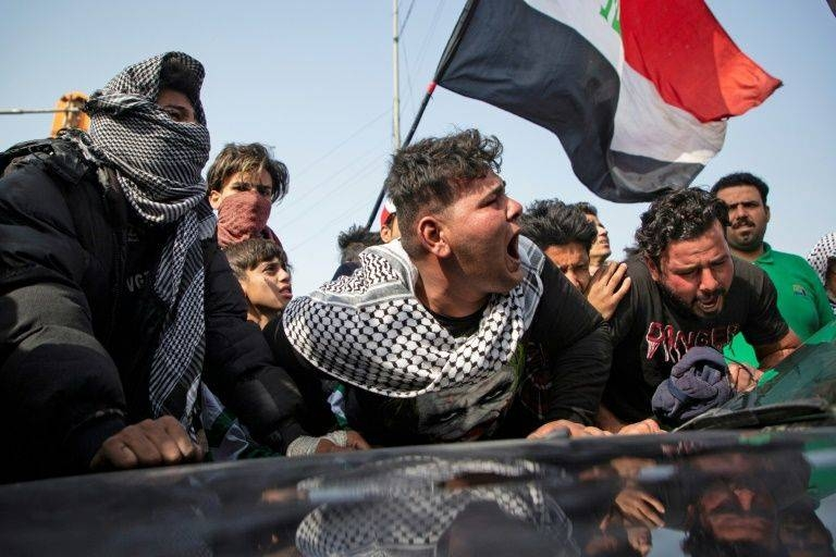 Angry Iraqi demonstrators mourn the killing of female activist and paramedic Janat Madhi, in Basra on Tuesday night, part of an upsurge of violence against the three-month-old protest movement. — AFP