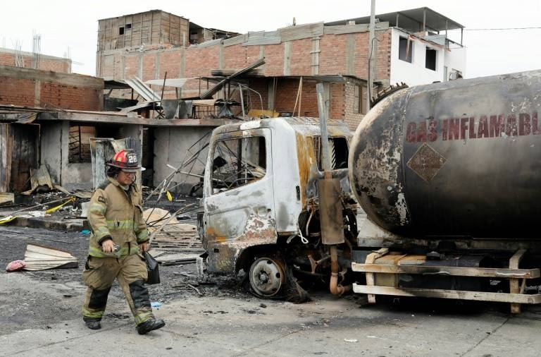 A fireman walks past the tanker truck that exploded in a Lima neighborhood, killing several people and igniting houses and cars in this on Jan. 23, 2020 file photo. — AFP