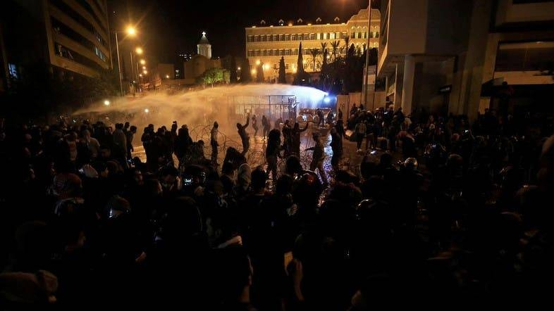 Demonstrators are sprayed by a water cannon during a protest against the newly formed government outside the government headquarters in downtown Beirut. — Courtesy photo