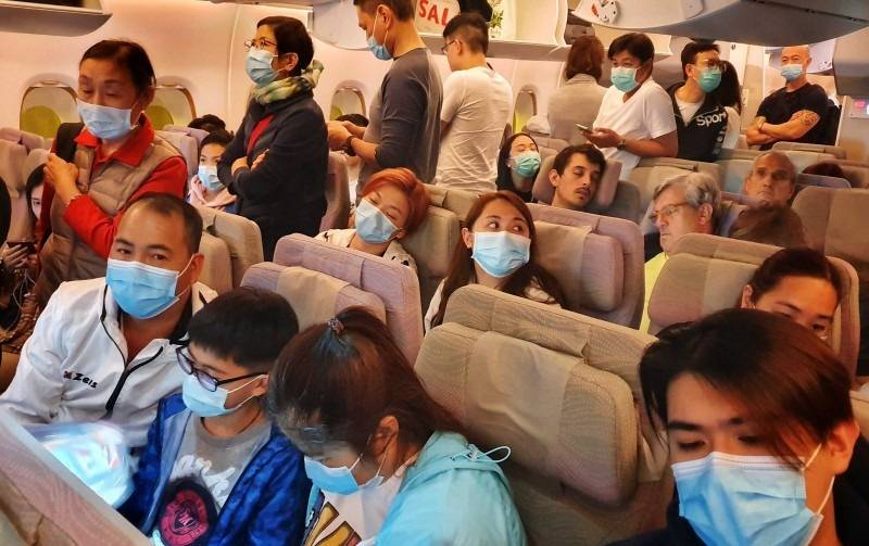 Passengers wear masks prepare to disembark from a flight from Hong Kong on arrival at Bangkok's airport ahead of the Chinese New Year in Bangkok in this Jan. 23, 2020 file photo. — AFP