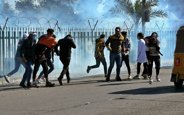 Anti-government protesters run as security forces fire tear gas to disperse them during clashes in Baghdad, Sunday. Courtesy photo