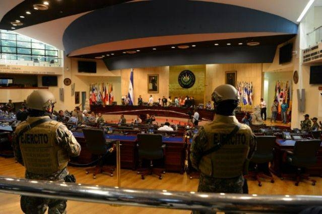 Before Mayib Bukele's entry, armed police and soldiers with rifles and wearing body armor entered the chamber. — AFP