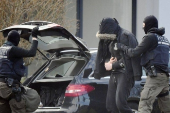 Police officers bringing a man believed to be one of the twelve men arrested in a nationwide probe against far-right activists, at the Federal Supreme Court in Karlsruhe, southern Germany, in this Feb 15, 2020 file photo. — AFP