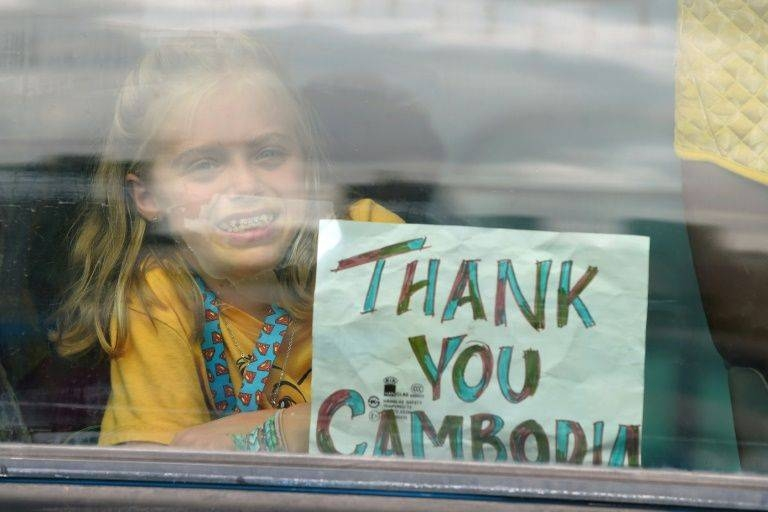 A young passenger from the Westerdam cruise ship holds up a sign on a bus after disembarking in Sihanoukville, Cambodia. — AFP