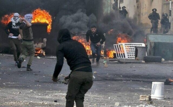 Palestinians clash with Israeli security forces during the funeral of Palestinian policeman Tareq Badwa, in the northern West Bank village of Azzun, earlier this month. — Archives