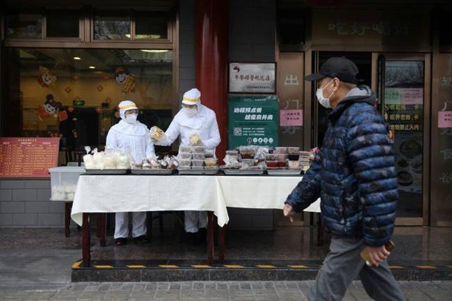 Restaurant workers wear protective clothing as they prepare food to sell on the street outside their restaurant in Beijing. — AFP