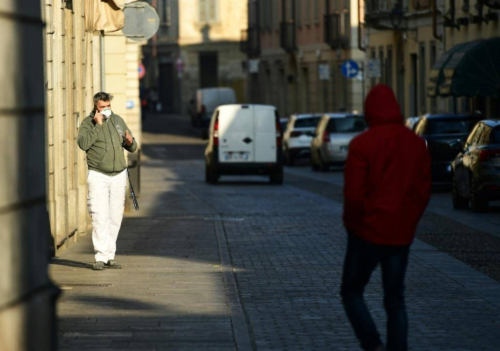 A resident wearing a protective mask in a street of Codogno, southeast of Milan. — AFP