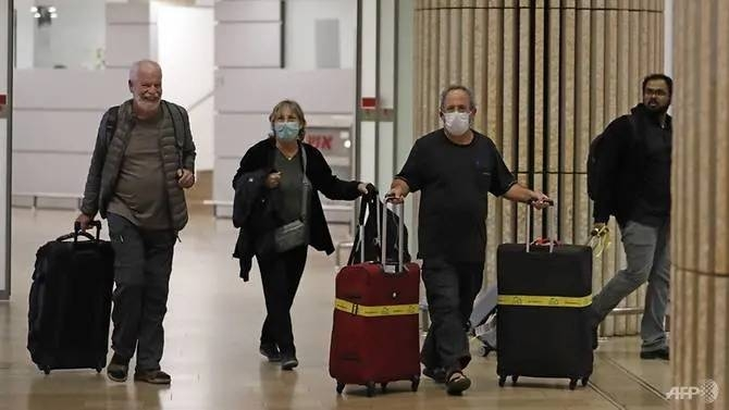 Passengers wearing protective masks walk at the arrival hall of Ben Gurion International Airport in Israel. — Courtesy photo