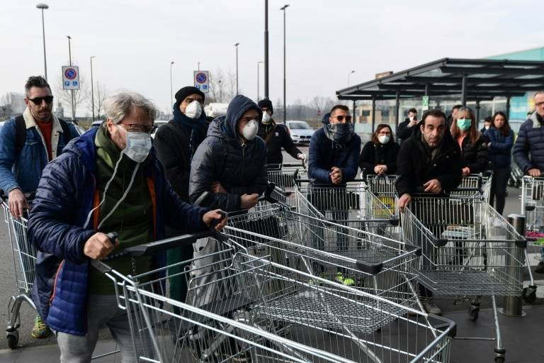 Residents wait to be alowed into a supermarket in groups in the small northern Italian town of Casalpusterlengo as the number of COVID-19 cases mounts. — AFP